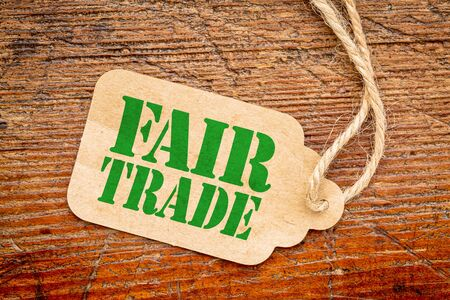 wood trade: fair trade sign a paper price tag against rustic red painted barn wood - conscious shopping concept