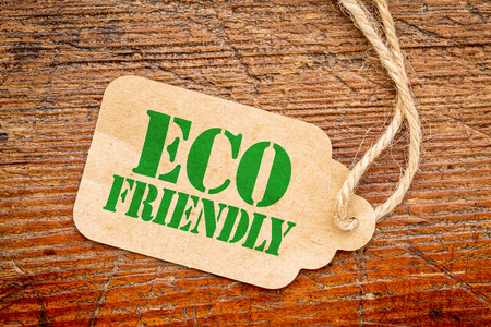 friendly: eco friendly  sign a paper price tag against rustic red painted barn wood - shopping concept