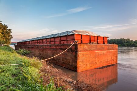 water transportation: red and rusty barge with a cover at a shore of Missouri River near Hermann, MO