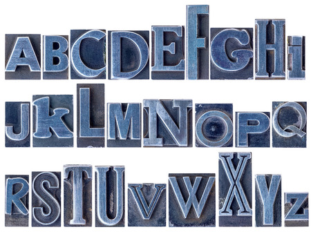 letterpress type: English alphabet - a collage of 26 isolated letters in letterpress metal type printing blocks, a variety of mixed fonts stained by blue ink