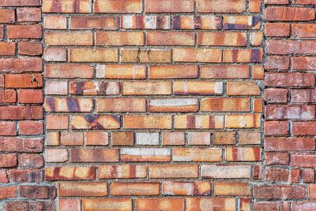 old brick wall background texture with a window covered by different bricks
