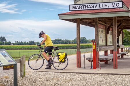 bike trail: MARHTSVILLE, MO, USA - AUGUST 1, 2015: A touring cyclist at Marthasville stop on Katy Trail (237 mile bike trail stretching across most of the state of Missouri converted from abandoned railroad)