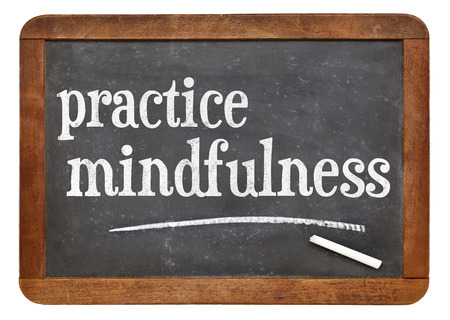 Practice mindfulness - motto or resolution on a vintage slate blackboard