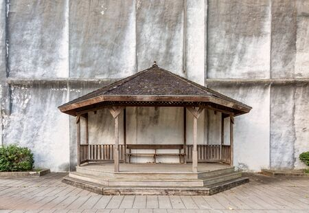 building wall: wooden gazebo with a bench against building wall in a street park, copy space