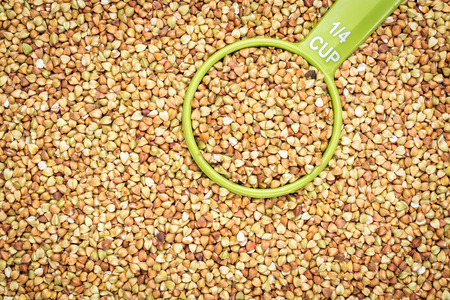 kasha: background and texture of buckwheat kasha with a measuring scoop - gluten free grain