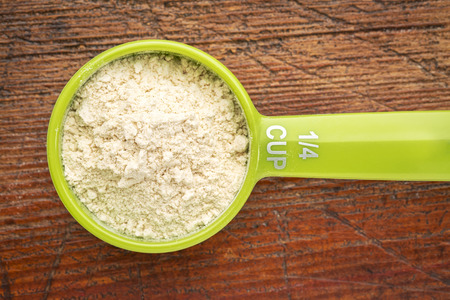 measuring scoop of whey protein powder against rustic scratched wood background