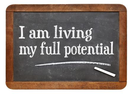 affirmation: I am living my full potential positive affirmation words on a vintage slate blackboard
