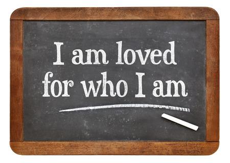 loved: I am loved for who I am - positive affirmation words on a vintage slate blackboard