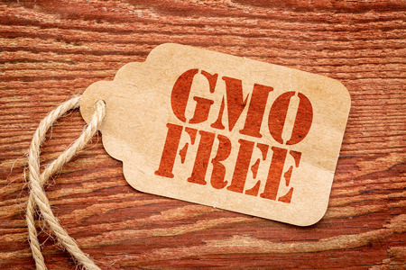GMO free sign - a paper price tag against rustic red painted barn wood