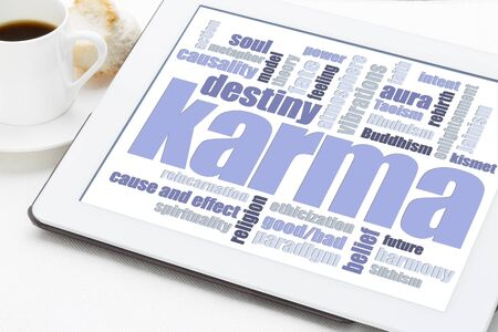 karma word cloud on a digital tablet with a cup of coffee - spiritual concept