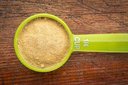 maca: maca root powder on a measuring scoop against rustic wood