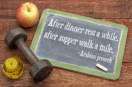 proverb: After dinner rest a while, after supper walk a mile -  Arabic proverb on a  slate blackboard sign against weathered red painted barn wood with a dumbbell, apple and tape measure - healthy living concept Stock Photo