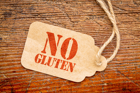 No gluten sign - a paper price tag against rustic red painted barn wood