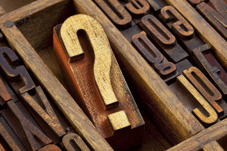 questions: question mark - vintage wooden letterpress type block in old typesetter drawer among other letters stained by color inks Stock Photo