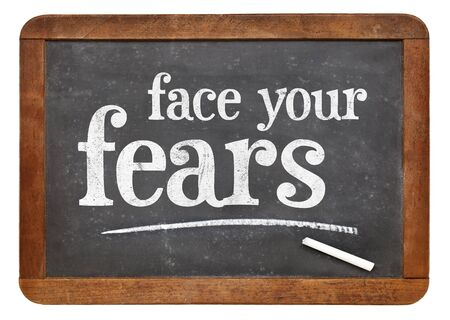 fear: Face your fears advice on a vintage slate blackboard isolated on white Stock Photo