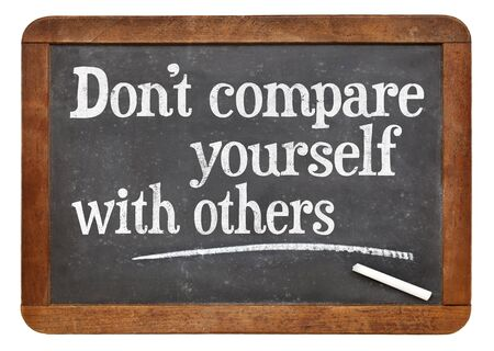 Do not compare yourself with others- motivational advice  on a vintage slate blackboard Banco de Imagens
