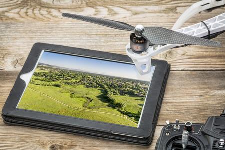 항공 사진 개념 드론 - 무인 항공기의 로터와 무선 제어 송신기와 디지털 태블릿에서 포트 콜린스 근처 콜로라도 산기슭의 항공 사진을 검토, 스톡 콘텐츠