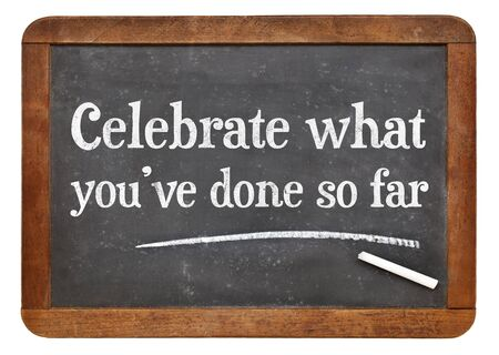 celebrate: Celebrate what you have done so far - white chalk text on a vintage slate blackboard