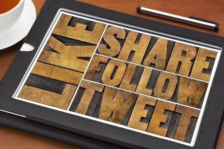 like, share, tweet, follow words-- social media and networking concept - text in letterpress wood printing blocks on a digital tablet with a cup of coffee Stock Photo
