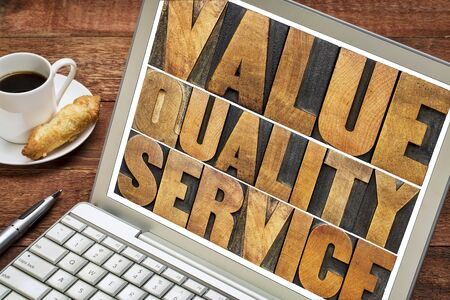 motto: value, quality, service - business mantra or motto concept - words in vintage letterpress wood type on a laptop screen with a cup of coffee