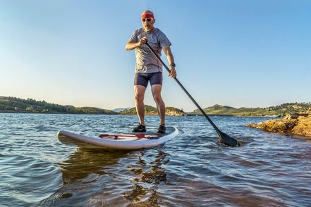 horsetooth reservoir: senior male paddler enjoying stand up paddling on a sunny summer day - Horsetooth Reservoir, Fort Collins, Colorado