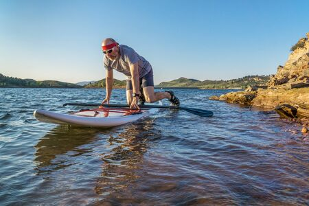 collins: male paddler starting stand up paddling on a rocky shore of Horsetooth Reservoir, Fort Collins, Colorado, summer scenery