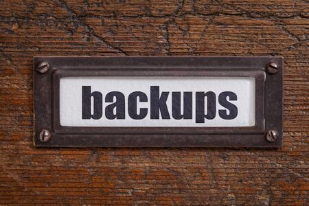backups: backups - a label on a grunge wooden file cabinet Stock Photo