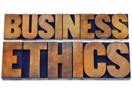 wood type: business ethics - isolated text in letterpress wood type printing blocks stained by color inks Stock Photo