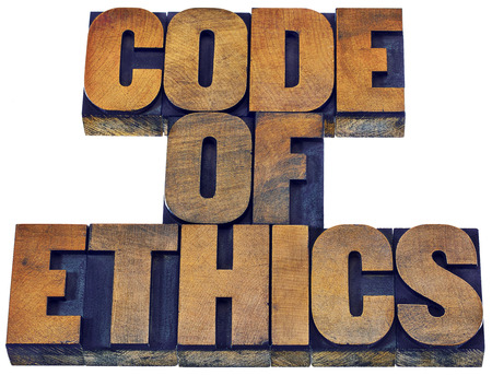 wood type: code of ethics word abstract - isolated text in letterpress wood type printing blocks stained by inks