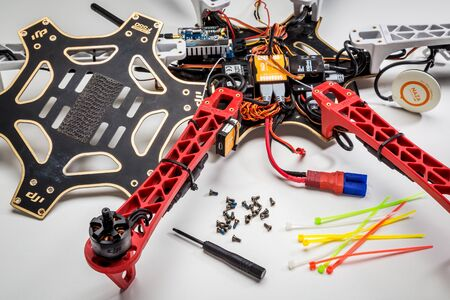FORT COLLINS, CO, USA, JULY 20,  2015:  Repairing and rebuilding a drone after a crash - a partially disassembled DJI F550 Flame Wheel hexacopter with a  screwdriver and screws in front. Publikacyjne