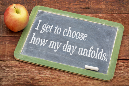 I get to choose how my day unfolds - positive affirmation phrase on a slate blackboard with a white chalk and a stack of books against rustic wooden table