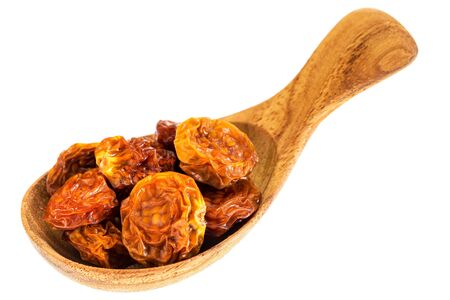 superfruit: dried goldenberries on a small wooden spoon isolated on white