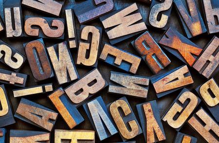 randomly: alphabet background - vintage letterpress wood printing blocks placed randomly on a grunge metal tray Stock Photo