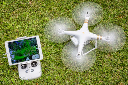 phantom: FORT COLLINS, CO, USA - AUGUST 28, 2015:  Spinning propellers and getting ready to take off. DJI Phantom 3 hexacopter drone with radio controller and iPad Air on grass area.