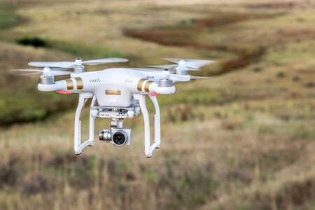 fort collins: FORT COLLINS, CO, USA, AUGUST 28, 2015:  Airborne radio controlled Phantom 3 quadcopter drone flying with a camera over prairie.