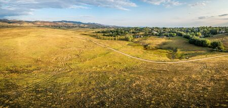 loveland: aerial panorama of foothills prairie along Front Range of Rocky Mountains near Fort Collins, Colorado, summer scenery lit by sunrise - - Cathy Fromme Prairie Natural Area with a bike trail