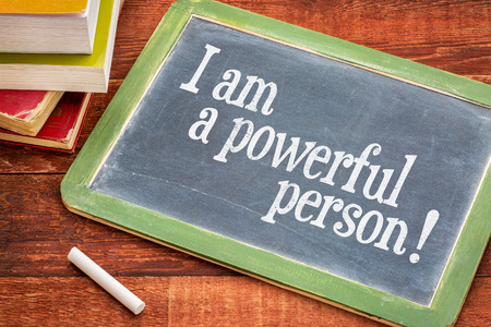 I am a powerful person - positive affirmation words on a slate blackboard with chalk and books