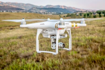 phantom: FORT COLLINS, CO, USA, SEPTEMBER 1, 2015:  Radio controlled Phantom 3 quadcopter drone is flying with a camera over foothills of Rocky Mountains. Editorial