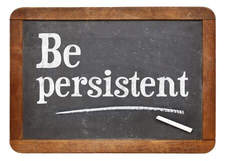 persistent: Be persistent - motivational advice on a vintage slate blackboard Stock Photo