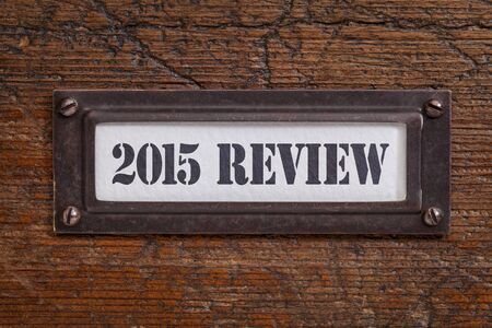 review: 2015 review - a label on wgrunge wooden file cabinet. A passing year summary and review concept.