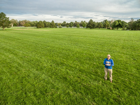 aerial: aerial shot of a male drone operator with a remote radio controller on a green grassy field Stock Photo