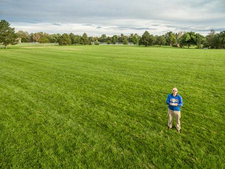 piloto: vista a�rea de un operador drone macho con un controlador remoto de radio en un campo de hierba verde Foto de archivo