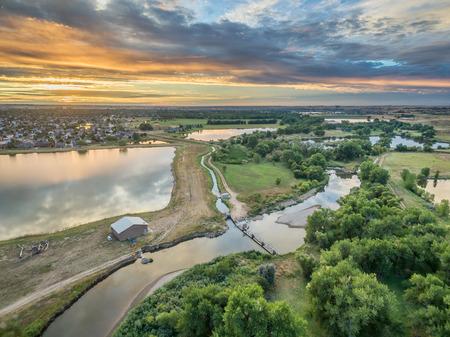 Luchtfoto van zonsopgang boven Cache la Poudre rivier met omleiding dammen, irrigatie sloten en vijvers, Windsor, Colorado
