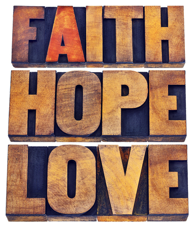 metaphysical: faith, hope and love - a collage of isolated words in vintage letterpress wood type stained by color inks