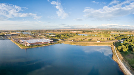 bike trail: aerial panorama of northern Colorado with a shopping mall, freeway, bike trail and numerous ponds and reservoirs with Front Range of Rocky Mountains ion a horizon