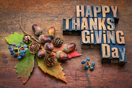 Happy Thanksgiving Day - text in vintage letterpress wood type with fall decoration (acorns, cones, leaf and vine berries) against rustic wood Stock Photo