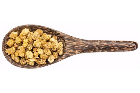 superfruit: dried white mulberries on a wooden spoon isolated on white - superfruit