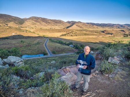 aerial shot of a male drone operator with a remote radio controller and monitor at Colorado foothills Stock fotó