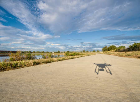 bike trail: shadow of a hexacopter drone flying low  with a camera over concrete bike trail Stock Photo