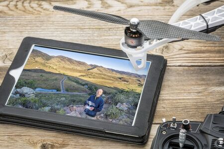 rotor: aerial photography concept - reviewing aerial picture of a drone operator on a digital tablet with a drone rotor and radio control transmitter